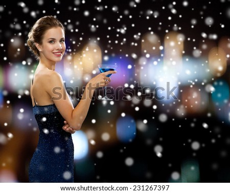 party, drinks, holidays, christmas and people concept - smiling woman in evening dress holding cocktail over night lights and snow background - stock photo