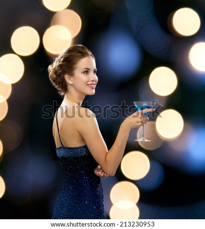 party, drinks, holidays, luxury and celebration concept - smiling woman in evening dress holding cocktail over night lights background - stock photo