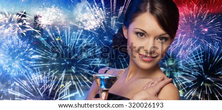 party, drinks, holidays, luxury and celebration concept - smiling woman in evening dress holding cocktail over nigh city and firework background - stock photo