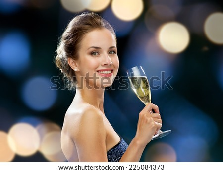 party, drinks, holidays, luxury and celebration concept - smiling woman in evening dress with glass of sparkling wine over night lights background - stock photo