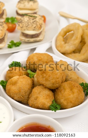 Party Food - Breaded Mushrooms, mini cheeseburgers and onion rings with chili sauce and sour cream and chives dip. - stock photo