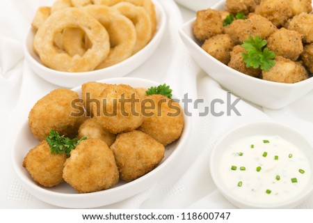 Party Food - Breaded mushrooms, popcorn chicken, onion rings served with sour cream and chives dip. - stock photo