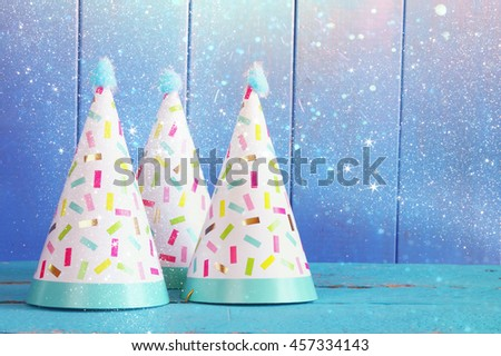 Party hat on wooden table. Glitter overlay - stock photo