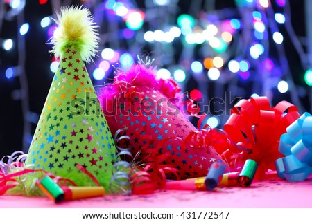 Party hats and other stuff on blurred garland background - stock photo