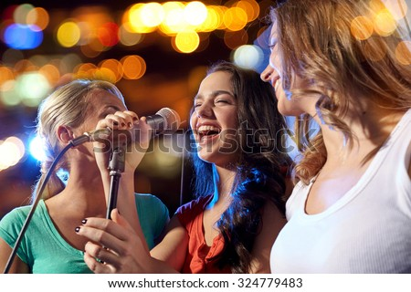 party, holidays, celebration, nightlife and people concept - happy young women singing karaoke in night club - stock photo