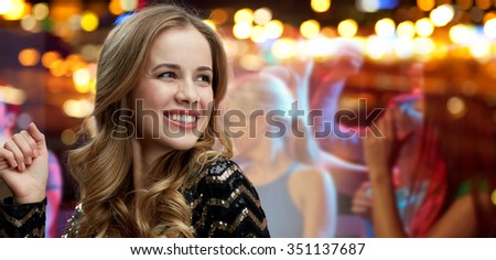 party, holidays, nightlife and people concept - face of happy young woman dancing over night club disco lights background - stock photo