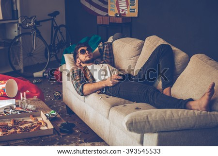 Party is over. Young handsome man in sunglasses lying down on sofa with joystick in his hand in messy room after party - stock photo