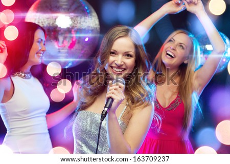 party, new year, celebration, friends, bachelorette party, birthday concept - three women in evening dresses dancing and singing karaoke - stock photo