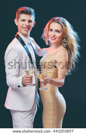 Party, romance and celebration. Studio portrait of happy gorgeous couple toasting with wineglasses. - stock photo