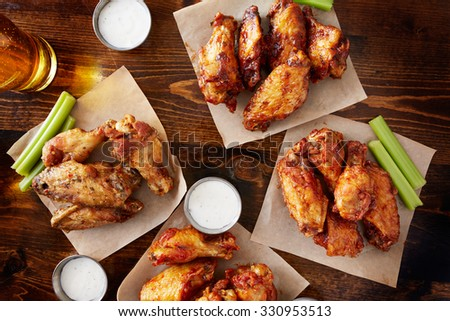 party sampler platter made to share with four different flavors of chicken wings served with beer and ranch dipping sauce - stock photo