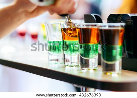 Party shots. Close up of beautiful shots coctails. Bartender pouring shots cocktails on the bar counter - stock photo