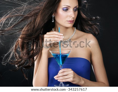 Party time. Beautiful woman with long hair holding martini glass.  - stock photo