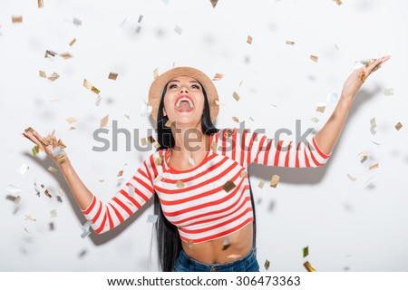 Party time! Cheerful young woman stretching out her hands while confetti falling on her - stock photo