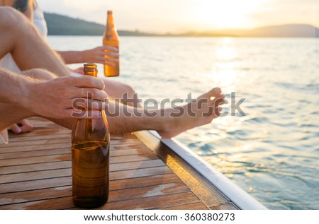 Party with friends. Close up male hand holding bottle of beer on the yacht sailing the sea. - stock photo