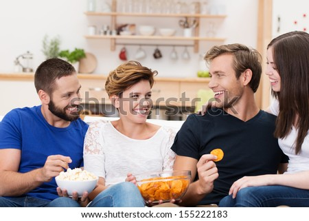 Partytime as a group of happy young men and women relax together on a sofa eating snacks and chatting - stock photo