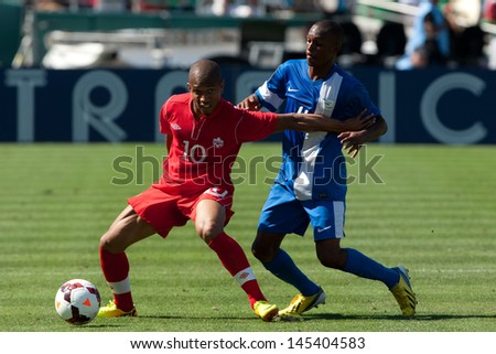 PASADENA, CA - JULY 7: Simeon Jackson #10 of Canada & Daniel Herelle #4 of Martinique during the 2013 CONCACAF Gold Cup game between Canada & Martinique on July 7, 2013 at the Rose Bowl in Pasadena. - stock photo