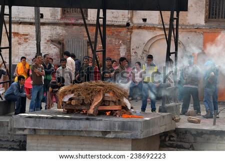 PASHUPATINATH - OCT 8: Cremation ghats and ceremony along the holy Bagmati River at Pashupatinath Temple, on Oct 8, 2013 in Kathmandu, Nepal. This is the most sacred place for all Hindus in Nepal  - stock photo