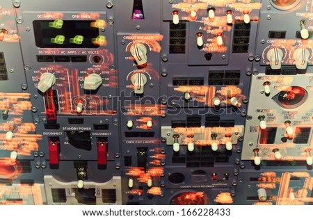Passenger aircraft cockpit dashboard during turbulence jolting. Lights in motion blur. Toned image - stock photo