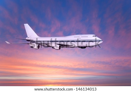 passenger airplane in the clouds at sunset or dawn. Tourist Card. plane on a background of sea and mountains. travel by air transport. flying to the top of the airliner. nobody - stock photo