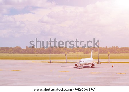 passenger airplane is landing to runway of airport, trees on background - stock photo