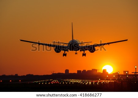 Passenger airplane is landing with a city skyline at the background. Sun is rising.  - stock photo
