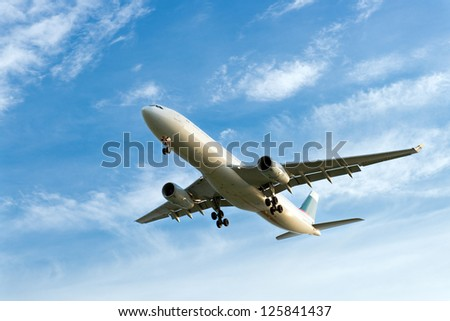 Passenger airplane landing against blue cloudy sky - stock photo
