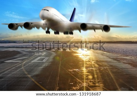 Passenger airplane landing on runway in airport. Evening. - stock photo