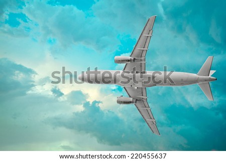 Passenger airplane on the beautiful cumulus clouds background - stock photo