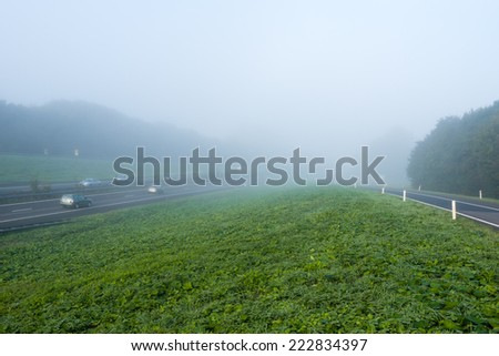 Passenger cars driving on a freeway in the Netherlands early on a foggy morning in the fall season. - stock photo