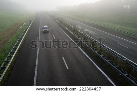 Passenger cars with burning headlights driving on a freeway in the Netherlands early on a foggy morning in the fall season. - stock photo
