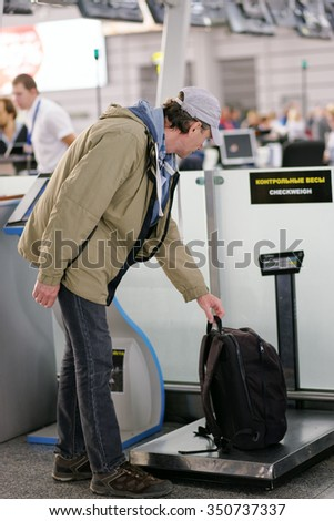 Passenger checking the weight of his luggage in the airport before the check-in - stock photo