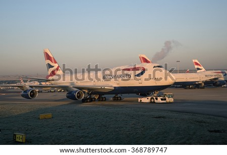 PASSENGER JET AT LONDON HEATHROW AIRPORT UK - CIRCA JANUARY 2016  A British Airways Jumbo passenger jet being towed by a tractor at sunrise at London Airport UK - stock photo