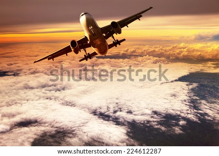 passenger jet plane take off to mid air against beautiful golden light of sun rising - stock photo