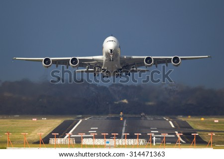 Passenger Jet taking off from a runway with dark clouds behind.  - stock photo