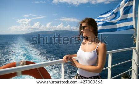 Passenger of greek cruise ship looking at sea and island - stock photo
