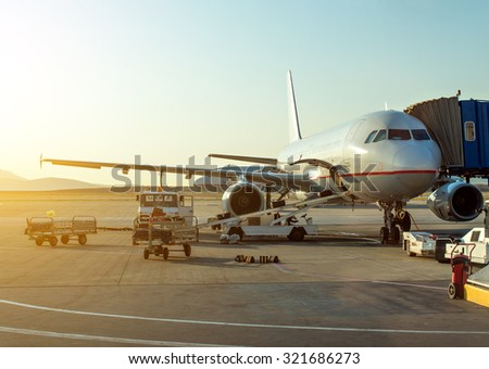 Passenger plane in the airport at sunrise. Aircraft maintenance. - stock photo