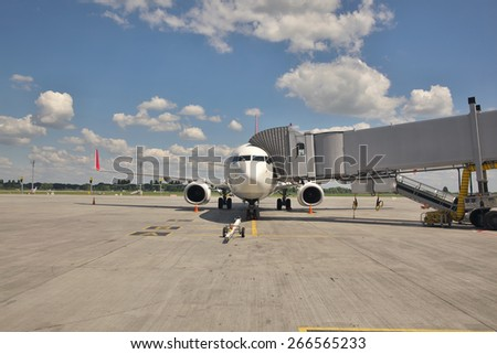 Passenger plane parked at the airport terminal boarding gate - stock photo