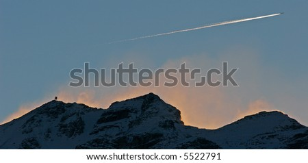 Passenger plane passing over Dolomite mountain - stock photo