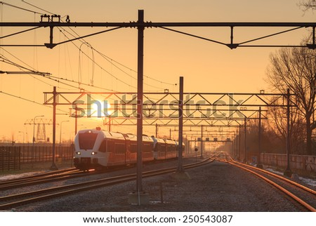 Passenger train and railroad tracks during a nice sunrise. - stock photo