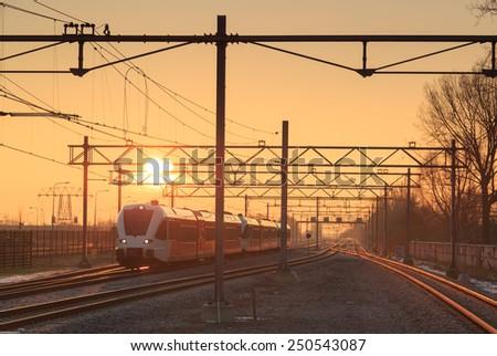 Passenger train and railroad tracks during a nice sunrise. - stock photo
