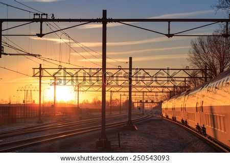 Passenger train and railroad tracks during a winter sunrise. - stock photo