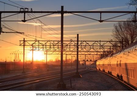 Passenger train and railroad tracks during a winter sunrise. - stock photo