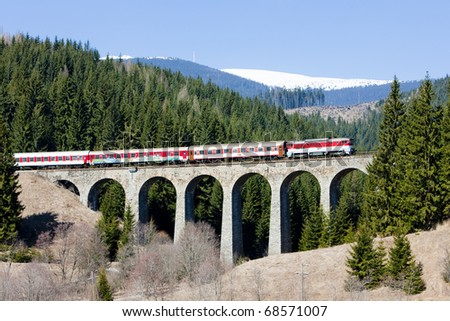 passenger train on railway viaduct near Telgart, Slovakia - stock photo