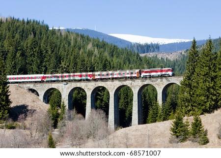 passenger train on railway viaduct near Telgart, Slovakia - stock photo