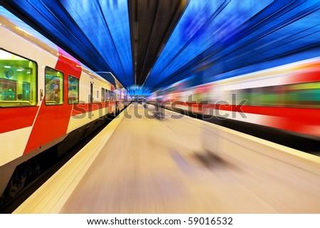 Passenger train passing railway station - stock photo
