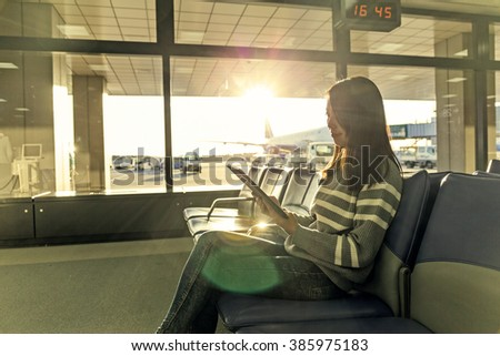 Passenger traveler woman in airport use of tablet at departure hall - stock photo