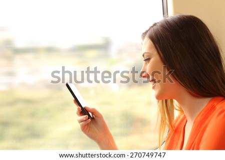 Passenger using a mobile phone in a train or bus beside the window - stock photo