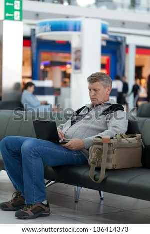 passenger waiting for flight works at the laptop - stock photo