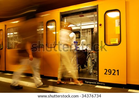 passengers and a woman in wheelchair in a berlin metro train - stock photo