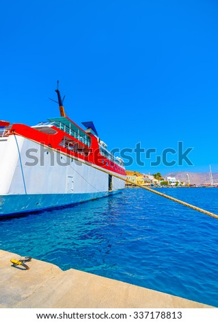 passengers ferry boat docked in the main port of Symi island in Greece - stock photo